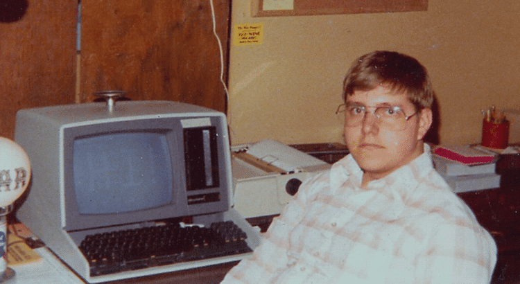Guy in classes and plaid shirt sitting at computer in the 80's
