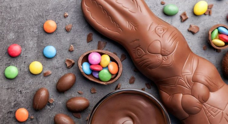 Chocolate Easter candy spread out on a table including a milk chocolate bunny and small colorful candy pieces